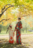 Attractive woman and little girl in a kimono walking in the Park Royalty Free Stock Images