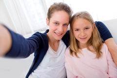 Attractive woman and little sister taking selfie Stock Image