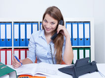 Attractive woman with long blond hair at office talking at phone Royalty Free Stock Photography