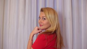 Attractive woman with long blond hair turning around and looking into camera. Attractive woman with long blond hair back view. Beautiful woman in red dress stock video footage