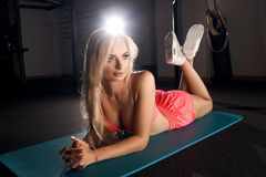 Female fitness model lying on exercise mat. Attractive woman with long blonde hair, dressed in pink sportswear and white sneakers, lying on her stomach with legs Royalty Free Stock Photography