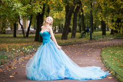 Attractive woman in long blue dress in park. Blond Royalty Free Stock Photography