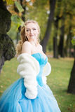 Attractive woman in long blue dress in park. Blond Royalty Free Stock Images