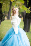 Attractive woman in long blue dress in park. Blond Stock Photo