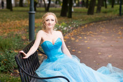 Attractive woman in long blue dress sitting in bench in park Stock Image