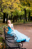 Attractive woman in long blue dress sitting in bench in park Stock Photo