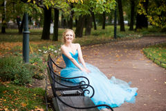 Attractive woman in long blue dress sitting in bench in park Stock Photos