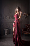 Attractive woman in long claret lace dress Stock Images
