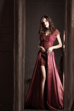 Attractive woman in long claret lace dress. Reflected in mirror Royalty Free Stock Image
