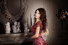 Attractive woman in long claret lace dress. Reflected in mirror. Vintage Royalty Free Stock Photography