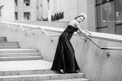 Attractive woman in long evening black dress posing on steps of. Granite staircase Royalty Free Stock Images