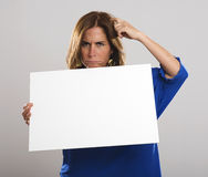 Attractive woman with long hair certainly makes gestures while holding a white sign. Woman Stock Image