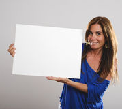 Attractive woman with long hair smiles at the camera while holding a white sign Royalty Free Stock Images