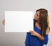 Attractive woman with long hair smiles while holding a white sign Stock Photo