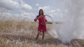 Attractive woman with long hair using fire extinguisher on the wheat field. Connection with nature, natural beauty