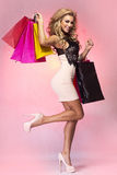Attractive woman looking at camera. Happy blonde woman posing with bags, shopping. Girl smiling , looking at camera stock photography