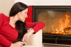 Attractive woman looking into fireplace cozy home Royalty Free Stock Image