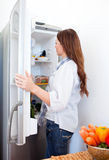 Attractive woman looking into the fridge. At home royalty free stock photo