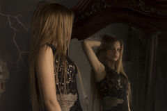 Attractive woman looking herself reflection in mirror Royalty Free Stock Images