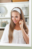 Attractive woman looking in the mirror Stock Photography