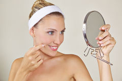 Attractive woman looking in mirror Stock Images