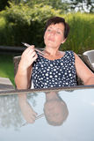 Attractive woman is looking sceptical on  e-cigarette in garden Stock Photos