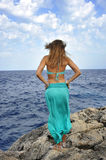 Attractive woman looking at sea horizon standing on rock cliff Stock Image