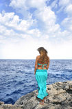 Attractive woman looking at sea horizon standing on rock cliff Royalty Free Stock Image