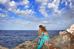 Attractive woman looking at sea horizon thoughtful from rock cliff  in relax concept Stock Photos
