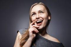 Attractive woman looking up over dark grey stock images