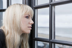Attractive woman looking through the window Stock Photos