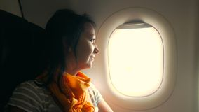 Attractive woman looks out of airplane window stock video footage