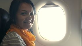 Attractive woman looks out of airplane window stock footage