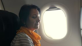 Attractive woman looks out of airplane window stock video