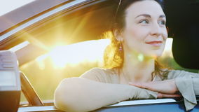 Attractive woman looks out the car window, portrait. Behind her are the rays of the setting sun. Happy driver