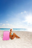 Attractive woman with luggage on the beach Stock Image