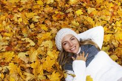 Attractive woman lying in autumn leaves royalty free stock photography