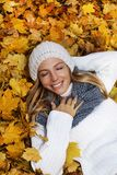 Attractive woman lying in autumn leaves royalty free stock photo