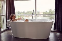 Attractive woman lying in bathtub royalty free stock images