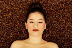 Attractive woman lying in coffee grains. Royalty Free Stock Photos