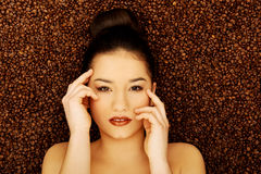 Attractive woman lying in coffee grains. Stock Image