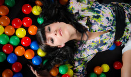 Attractive woman lying among colorful balls Stock Images