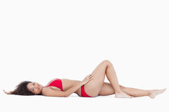 Attractive woman lying down while looking at the camera Royalty Free Stock Image