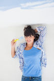 Attractive woman lying on floor holding paint brush overhead Stock Images