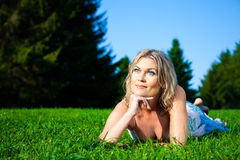 Attractive woman lying on green fresh grass Royalty Free Stock Images