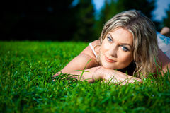 Attractive woman lying on green fresh grass Stock Photo