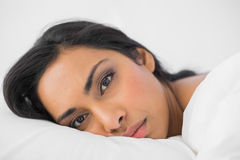 Attractive woman lying in her bed looking seriously at camera Stock Photo