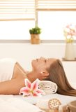 Attractive woman lying on massage bed in spa. Stock Photos