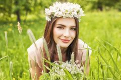 Attractive woman lying on meadow of green grass and flowers. Blossom summer portrait of beautiful female model with makeup and brown hair Royalty Free Stock Photography
