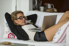 Attractive woman lying on sofa with laptop. Royalty Free Stock Photography